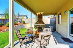 Cozy covered patio with stone trim fireplace. Glass top patio table and comfortabe chairs with stripped covers. Northwest USA